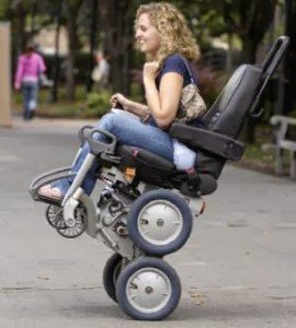 Outside at a park a woman is in an iBot chair that is on two small wheels only smiling